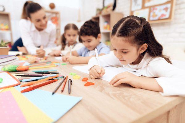 children-write-in-notebooks-with-pen-min
