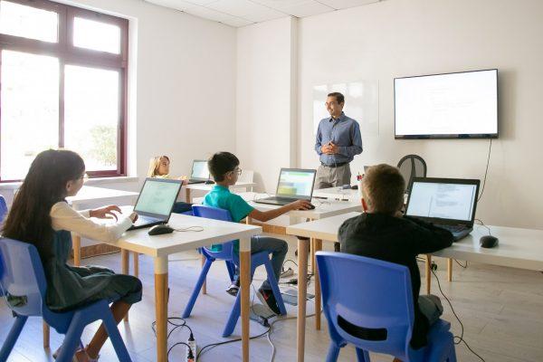 confident-teacher-explaining-lesson-to-pupils-min